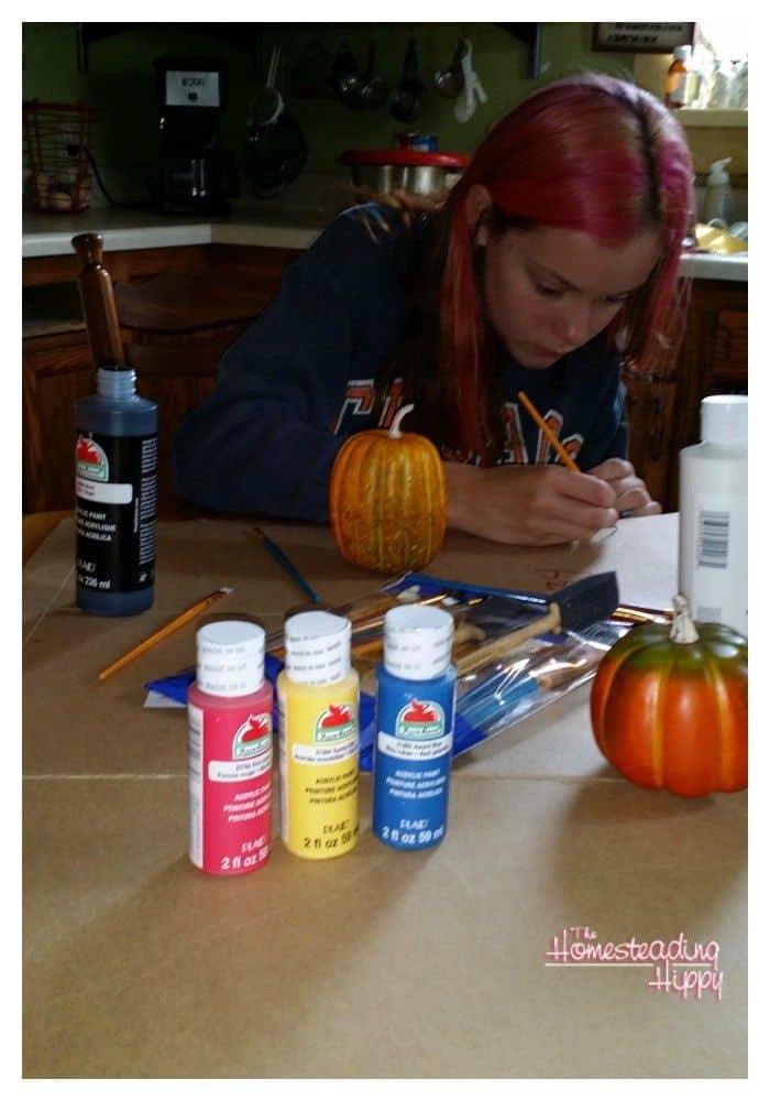 gilr painting a pumpkin