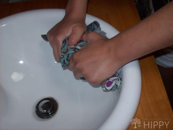squeezing water out of washed garment in sink