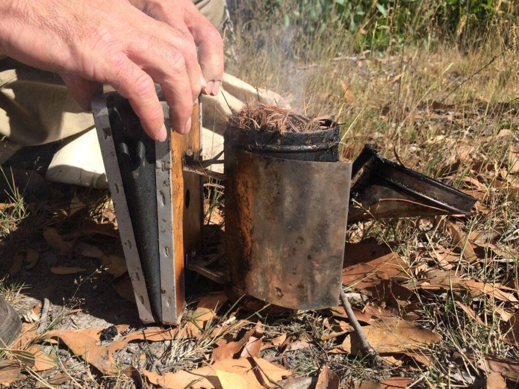 beekeeper using a smoker