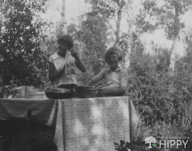 two pioneer girls cooking on outdoor table